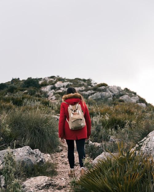 彼女のバックパックと山道を歩く若い女性の後姿 無料写真