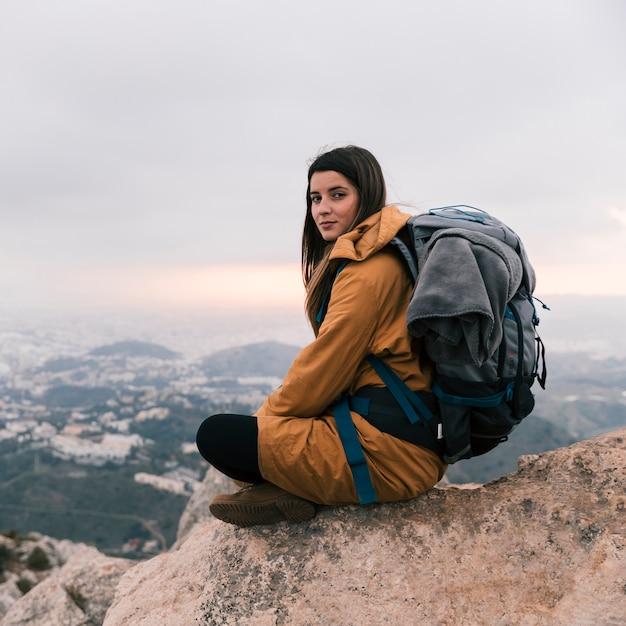 彼女のバックパックと山の端に座っている女性の若い女性 無料写真