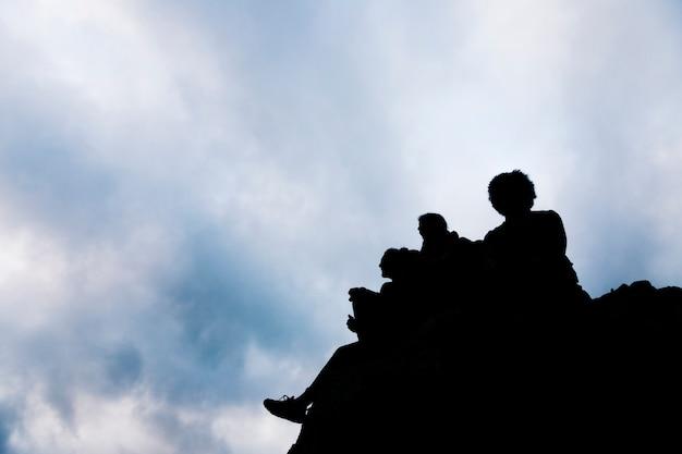 青い空を背景に岩の上に座っている友人のシルエット 無料写真