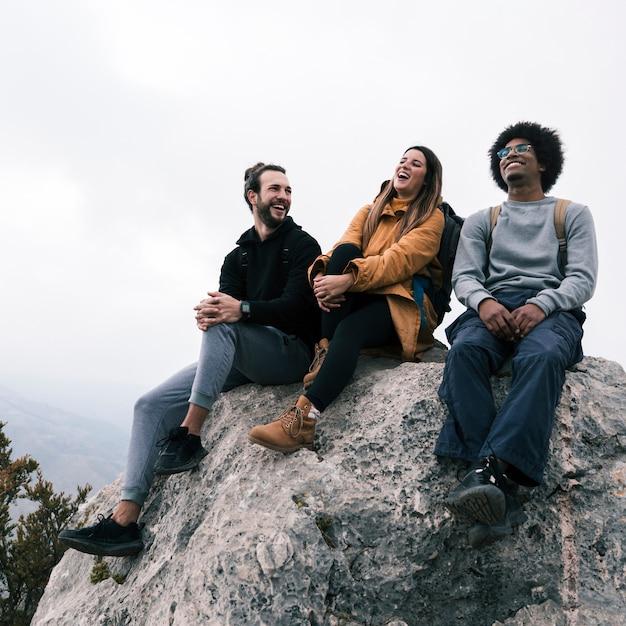 楽しんで岩の上に座っている若い女性と男性のハイカー 無料写真