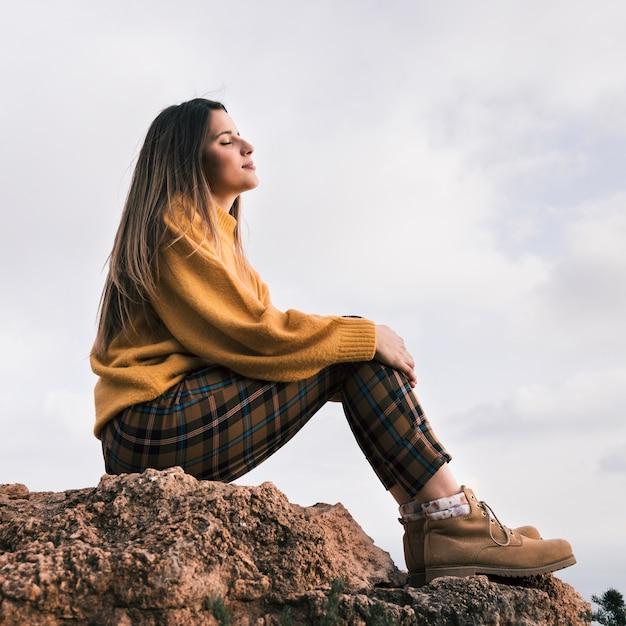 空に対して自然を楽しんでいる岩の上に座っている若い女性 無料写真