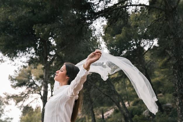 スカーフを飛んで、森の中の新鮮な空気を楽しんでいる彼女の手を上げる若い女性の側面図 無料写真