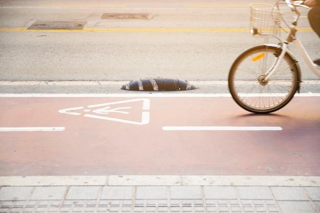 警告の三角形のサインが付いている道で自転車に乗る人のクローズアップ 無料写真