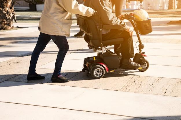 路上でモビリティスクーターの上に座っている男を押す人のクローズアップ 無料写真