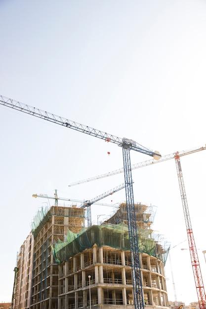 青と白の空を背景に建設用クレーン付き建物の低角度のビュー 無料写真