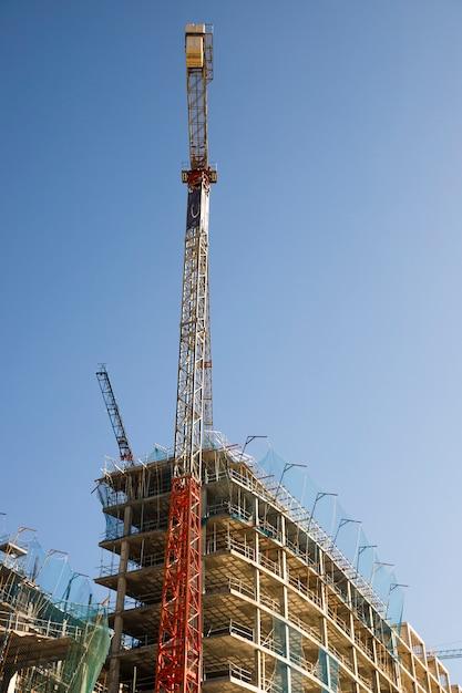 青い空を背景にサイトの近くの建設用クレーンの低角度のビュー 無料写真