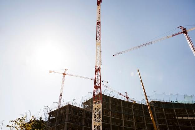 日光の下で青い空を背景に建設中の建物のシルエット 無料写真