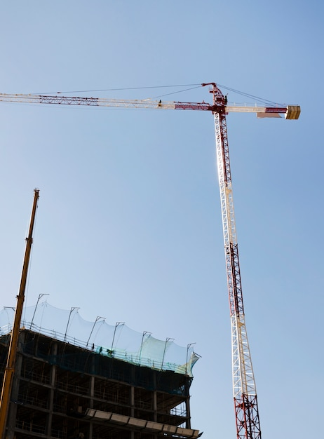 青い空を背景の建物の前に赤と白の建設用クレーン 無料写真