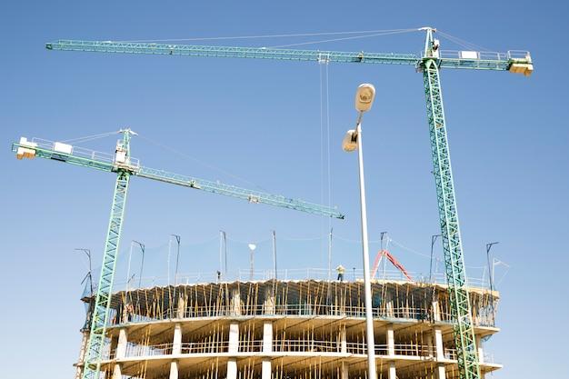クレーンと青い空を背景に建物の建設現場 無料写真