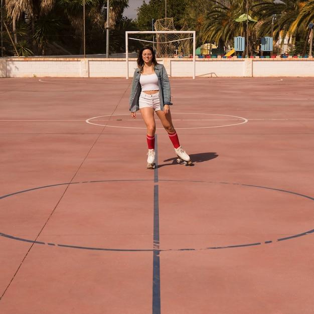 Молодая женщина на коньках на открытом футбольном поле Бесплатные Фотографии