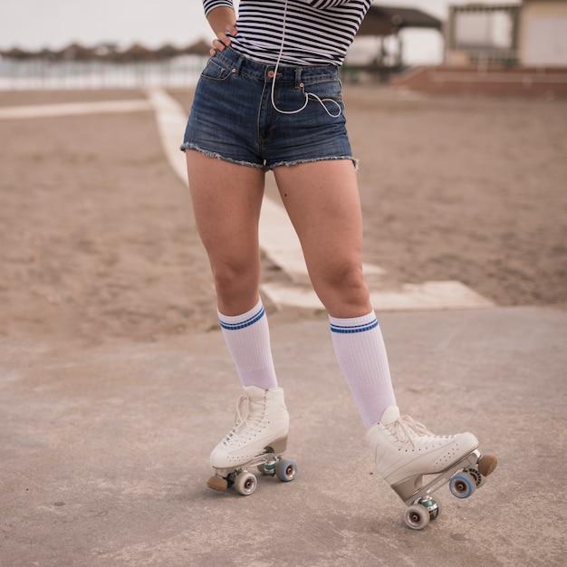 ビーチの上に立っている女性スケーターの低いセクション 無料写真