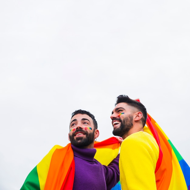 同方向を向いている虹色の旗と同性愛者の笑顔 無料写真