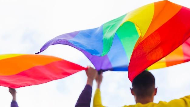 同性愛者がパレードで保持している手を振っている虹色の旗 無料写真