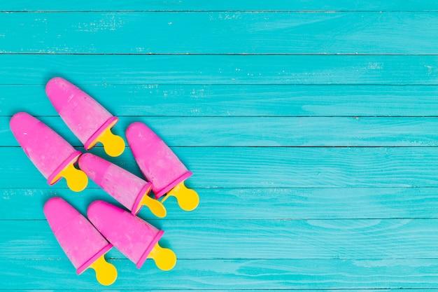 木製のターコイズブルーの背景に黄色の棒に明るいピンクのアイスキャンディー 無料写真