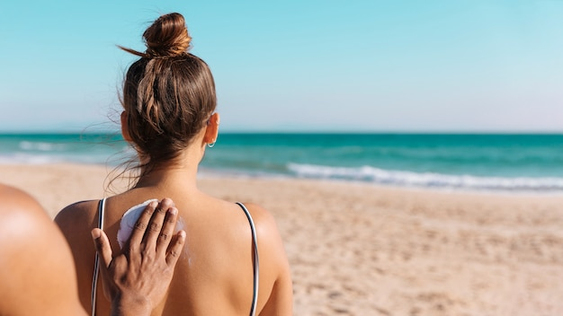 海岸の後ろのガールフレンドに日焼け止めクリームを入れて男 無料写真