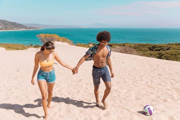 カップルはビーチの上を歩くと手を繋いでいます。 無料写真