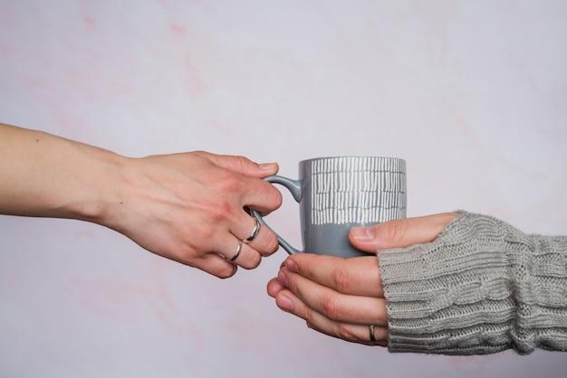 セーターの人にカップを与える手 無料写真