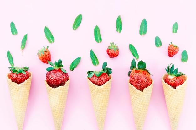 明るい背景にアイスクリームのワッフルコーンのイチゴ 無料写真