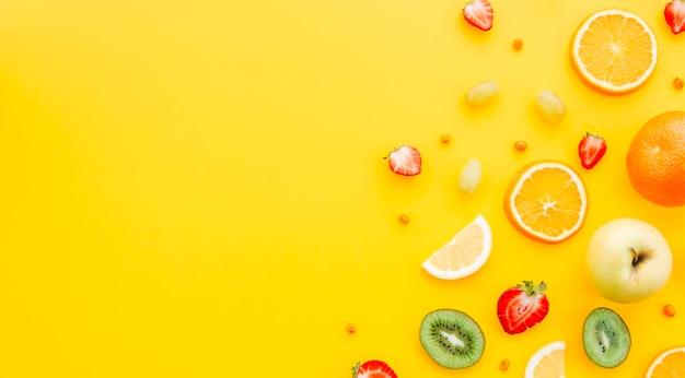 黄色の背景にカラフルなフルーツ 無料写真