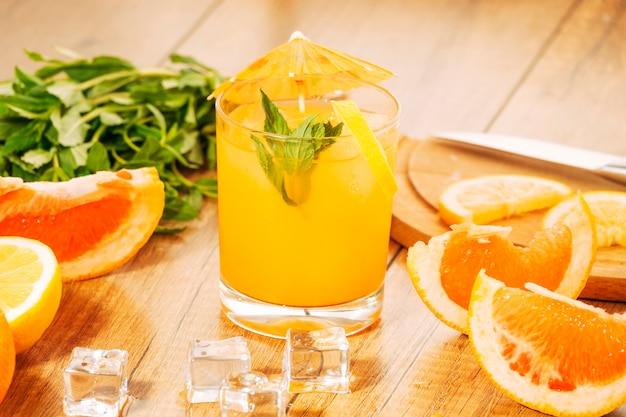 Разрезанные апельсиновые фрукты и сок с зонтиком Бесплатные Фотографии