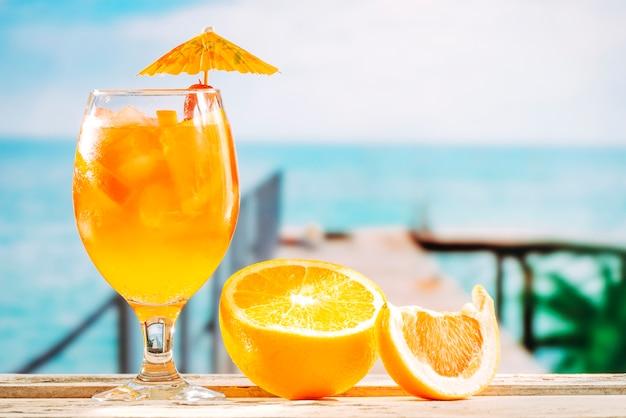 傘のガラスのオレンジ色の飲み物とスライスされたオレンジ色のテーブル 無料写真