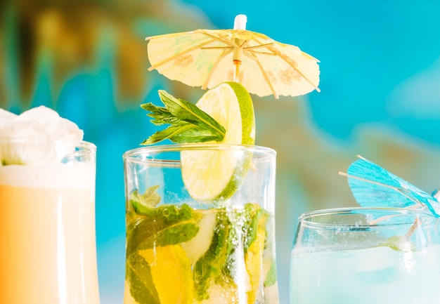 Свежий напиток с ломтиками лайма и мяты в стеклянном зонтике Бесплатные Фотографии