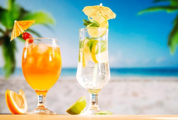 イチゴのオレンジ色の飲み物とスライスしたライムのお祝いに飾られたグラス 無料写真