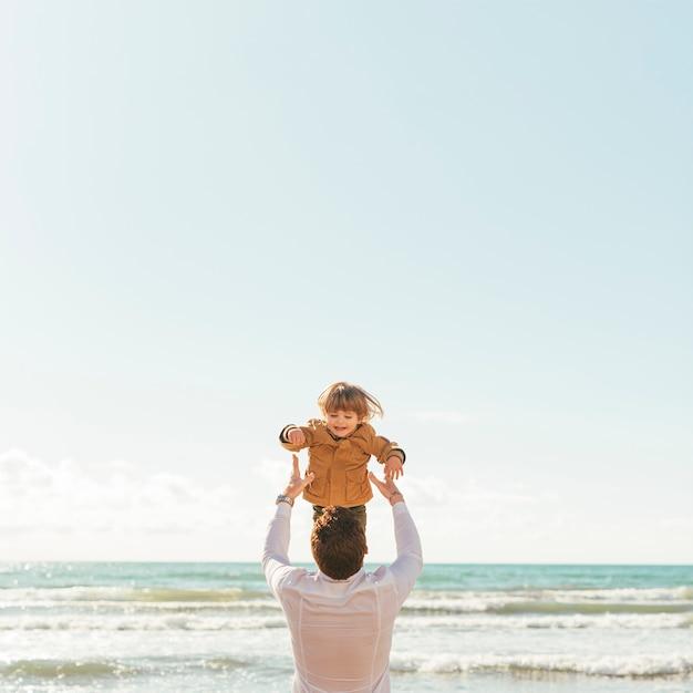 空に笑う幼児を投げる父 無料写真