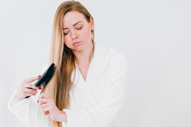 浴室で彼女の髪をブラッシングの女の子 無料写真