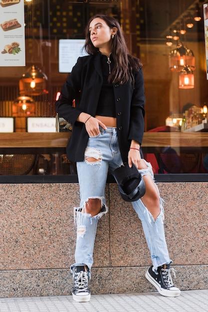 Молодая женщина, опираясь на стекло ресторана в рваных джинсах, держа в руке черную кепку Бесплатные Фотографии