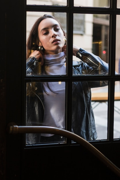 ガラスの前に立っている若い女性の肖像画 無料写真