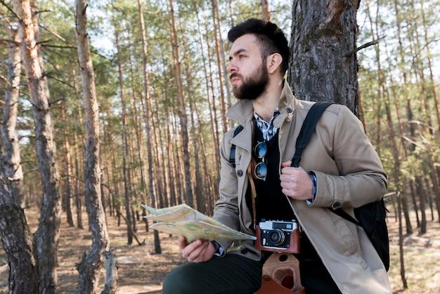 よそ見フォレスト内の一般的な地図を保持している男性のハイカーの肖像画 無料写真