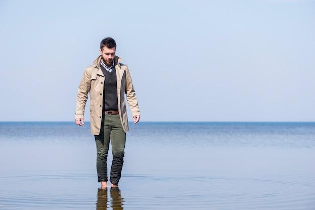 青い空を背景に浅い海の水の中を歩くスタイリッシュな若い男 無料写真
