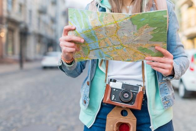 地図を手で保持しているカメラを持つ女性旅行者の半ばセクション 無料写真