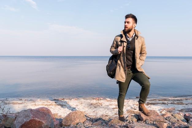 海の前に立っている肩にハンドバッグを持つ男性のハイカーの肖像画 無料写真