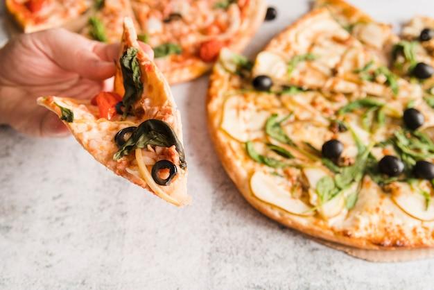 手のピザのスライス 無料写真