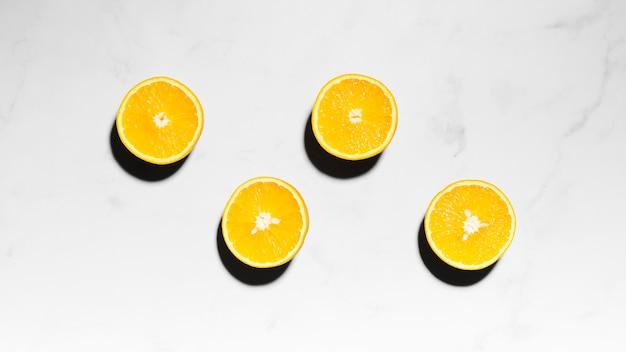 ジューシーオレンジは軽い表面に半分 無料写真