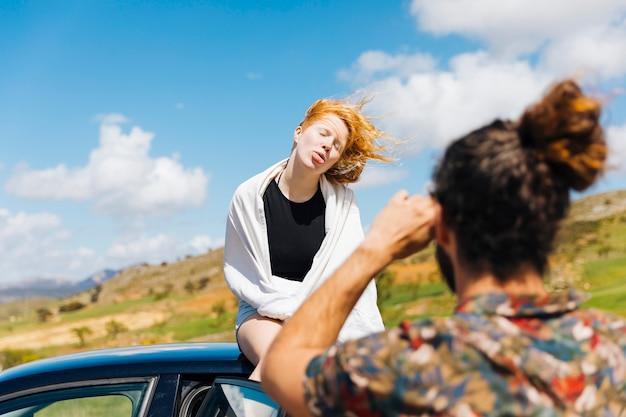 男は車の屋根の上に座って顔をゆがめた女性を撮影 無料写真