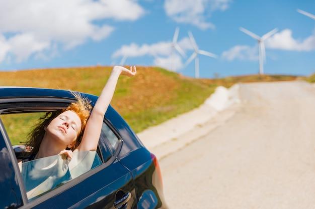 Молодая рыжая женщина, любящая жизнь из окна автомобиля Бесплатные Фотографии