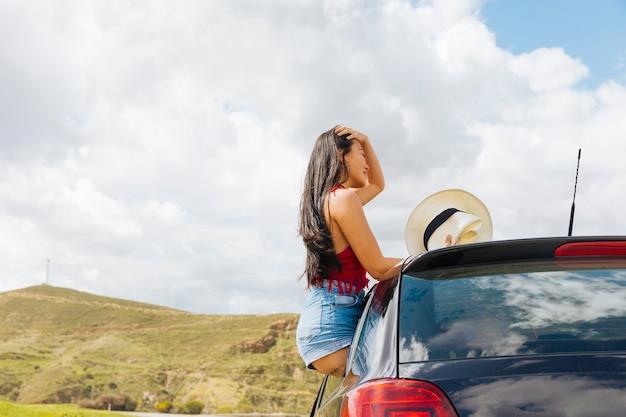 Привлекательная молодая женщина, сидя на автомобильной двери Бесплатные Фотографии