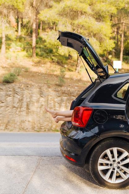 女性の足で車のトランクを開く 無料写真