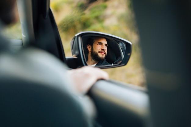 車のサイドミラーで幸せな男性の反射 無料写真
