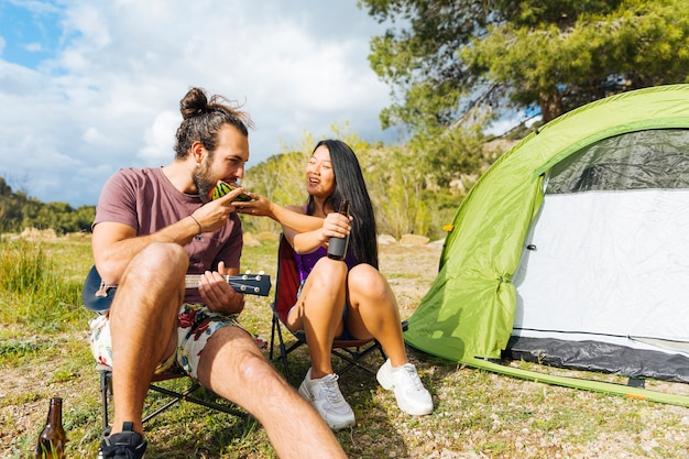 若いカップルが芝生の上でキャンプ 無料写真