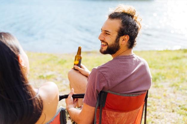Пара отдыхает с пивом на берегу реки Бесплатные Фотографии