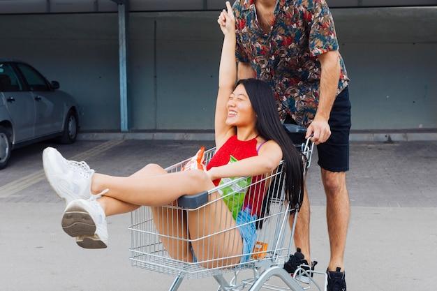 遊び心のあるカップルのショッピングトロリーに乗って 無料写真