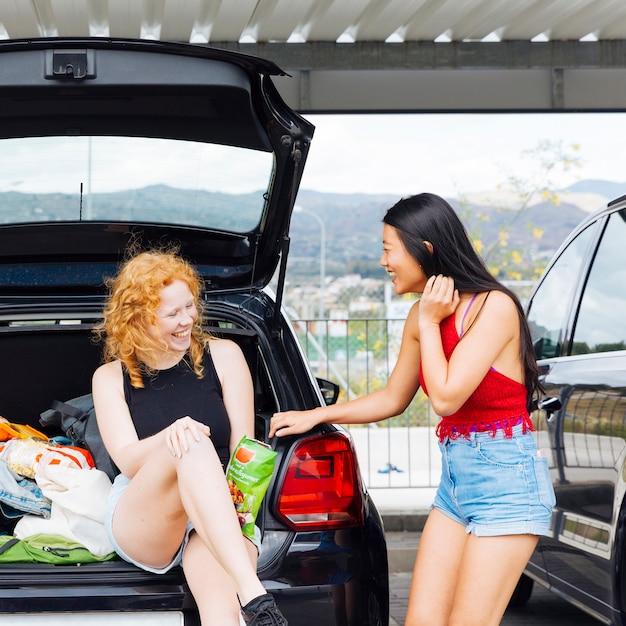 笑って車のトランクで楽しんでいる女性 無料写真