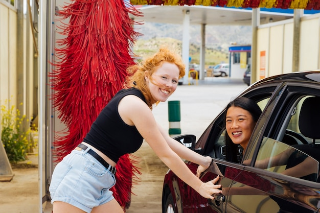 車の女性の近くに立って、カメラ目線の車の女性に座っています。 無料写真