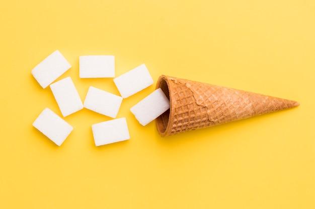 ワッフルコーンと黄色の背景に砂糖 無料写真