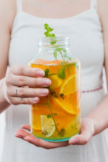 柑橘系の飲み物のボトルを保持している女性 無料写真