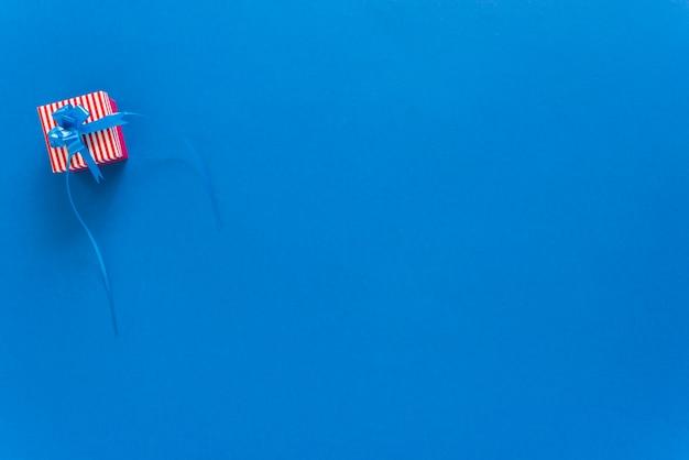 青色の背景に小さなギフトボックス 無料写真